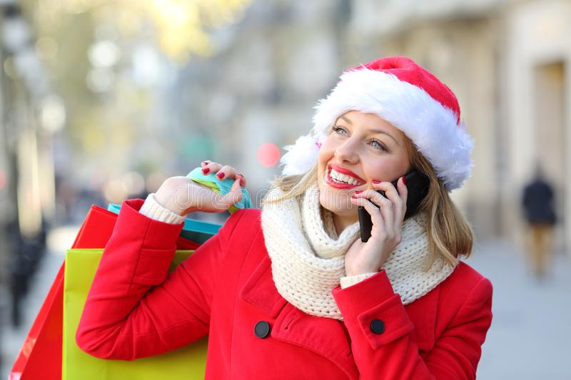 Happy shopper talking on phone on christmas. Happy shopper in red holding shopping bags talking on phone on christmas holidays on the street royalty free stock images