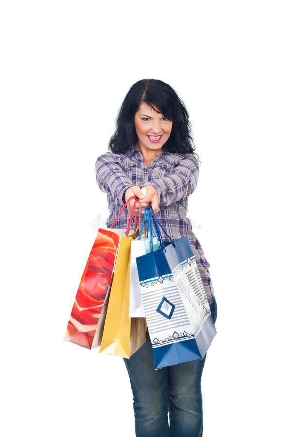 Happy shopper woman giving shopping bags stock photo