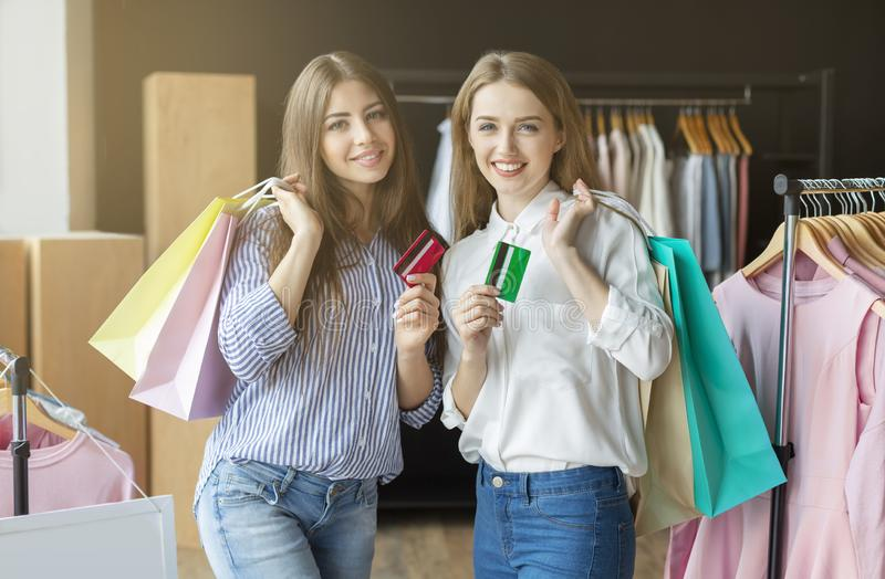 Happy shoppers holding credit cards posing with purchases at showroom stock photo