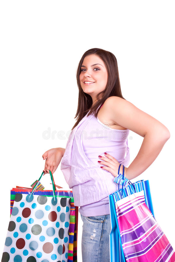 Happy shopping. Young happy brunette girl standing very satisfied with shopping paper bags royalty free stock photography
