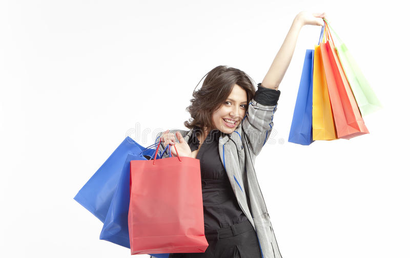 Happy shopping woman. Happy young woman holding colorful shopping bags in air royalty free stock photography