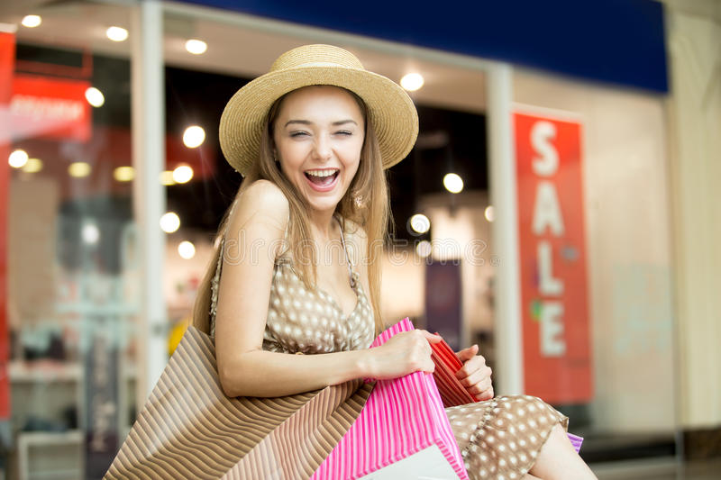 Happy shopping woman laughing squinted. Portrait of cheerful young pretty woman wearing hat in shopping centre, hugging tightly bags with purchases, laughing stock photos