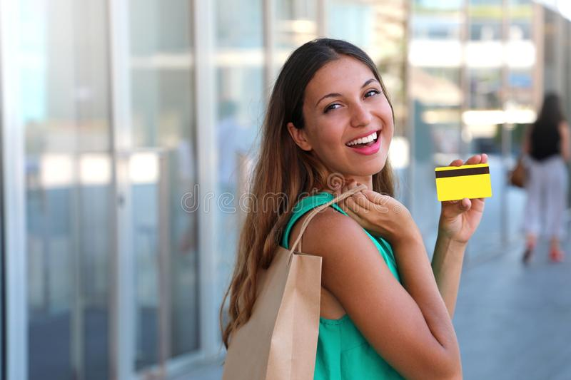 Happy shopping woman showing her credit card. Girl with shopper bag holding her credit card and show it at the camera. royalty free stock photos