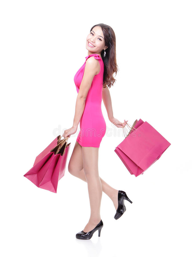 Happy shopping young woman running. With color bags - isolated on white background, full body, asian model stock photos
