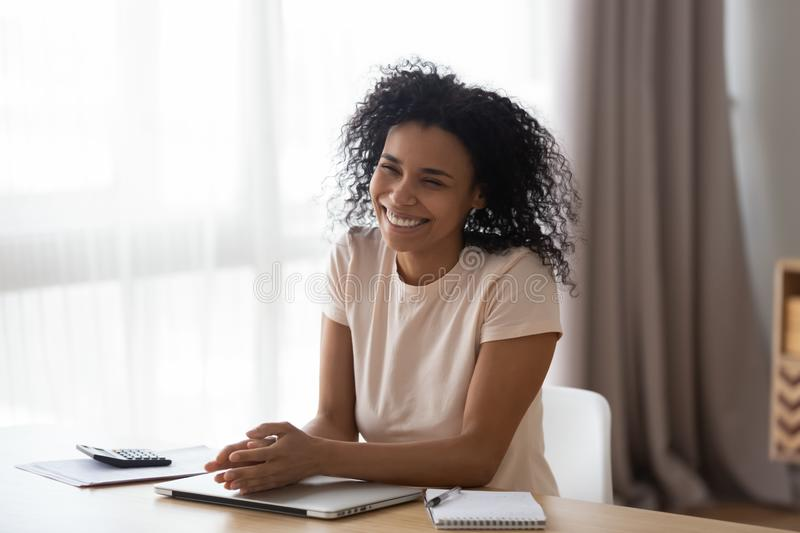 Happy young african woman laughing sitting at home office desk royalty free stock photography