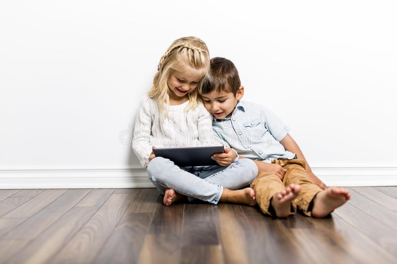 Happy siblings child playing with pc tablet together stock photos
