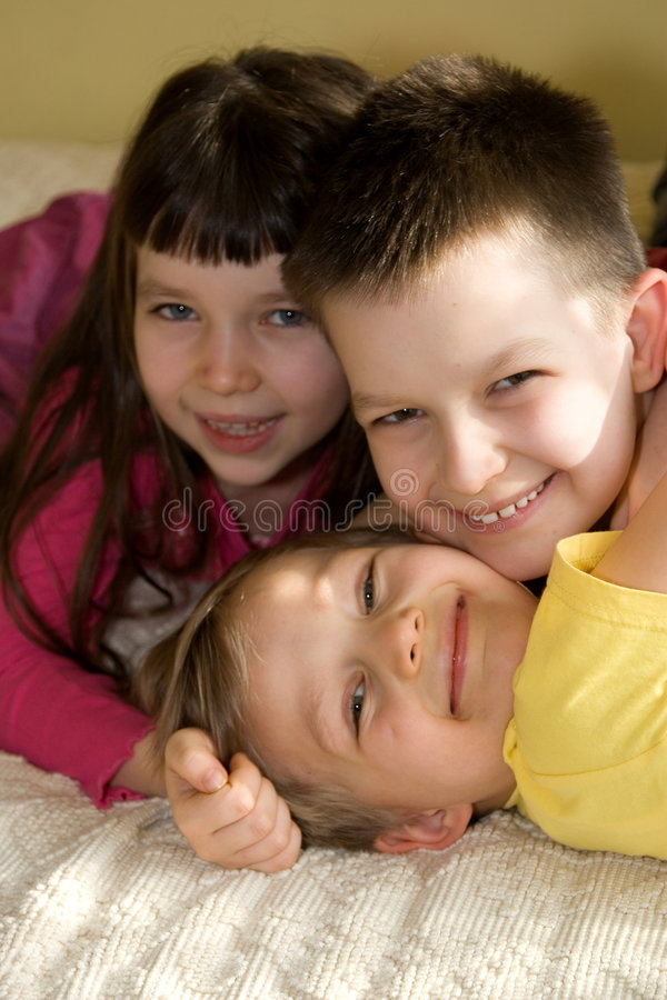 Happy Siblings At Home. Smiling portrait of a young girl and her two brothers, taken in a home setting stock photos