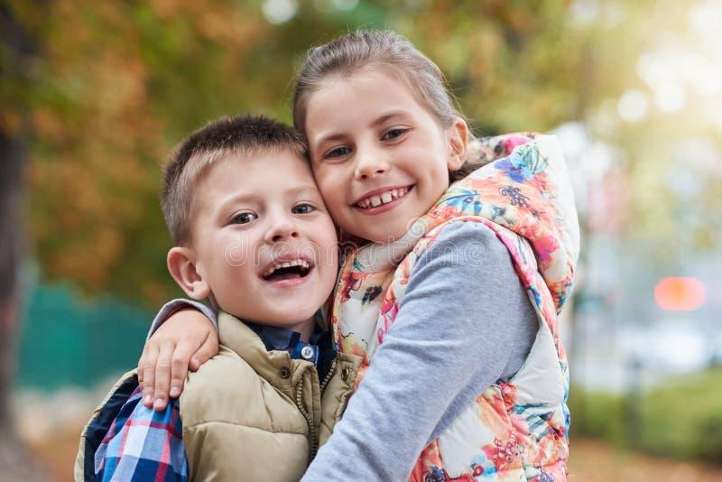 Happy siblings hugging outside stock photos