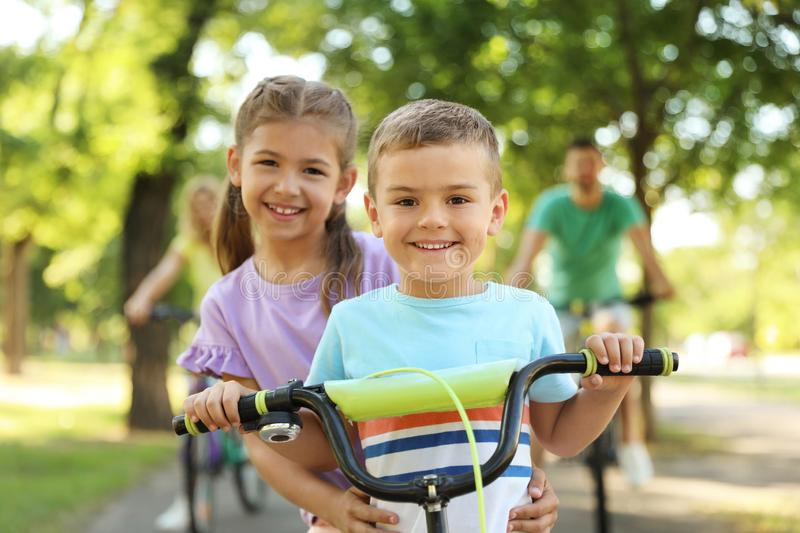 Happy siblings and  parents riding bicycles in park. Happy siblings and their parents riding bicycles in park stock photos