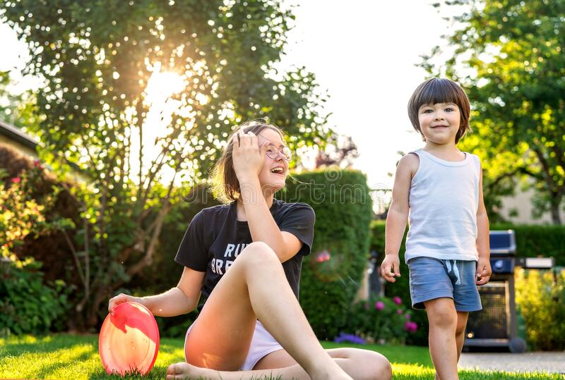 Happy siblings playing frisbee on green grass in garden backyard at sunset. Togetherness, little brother spending time with teen s stock photo