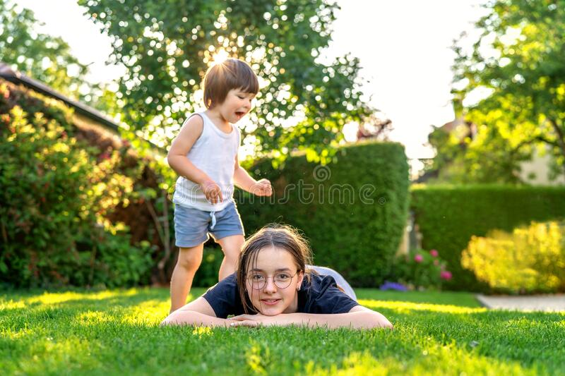 Happy siblings playing on green grass in garden backyard at sunset. stock photography