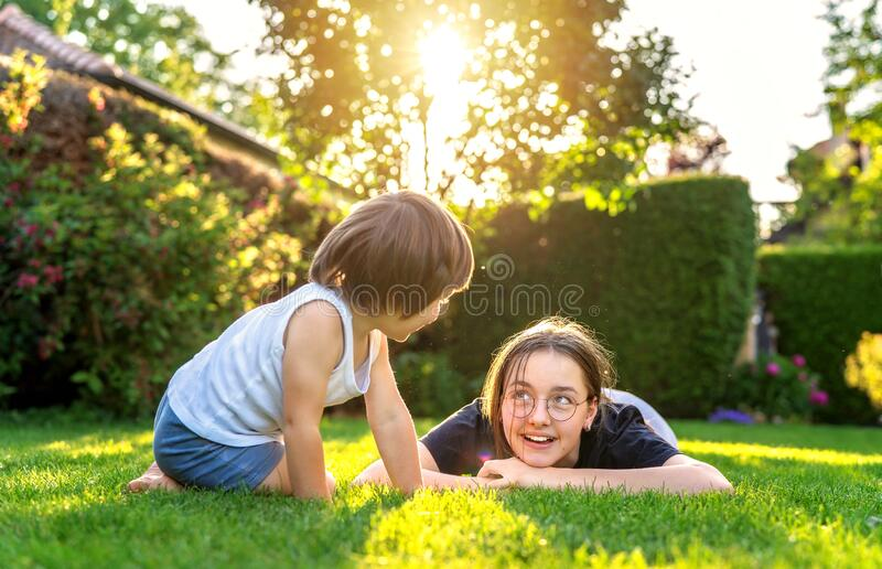 Happy siblings playing on green grass in garden backyard at sunset. Togetherness, little brother spending time with his teen siste royalty free stock image