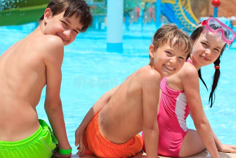 Happy siblings by pool royalty free stock photo