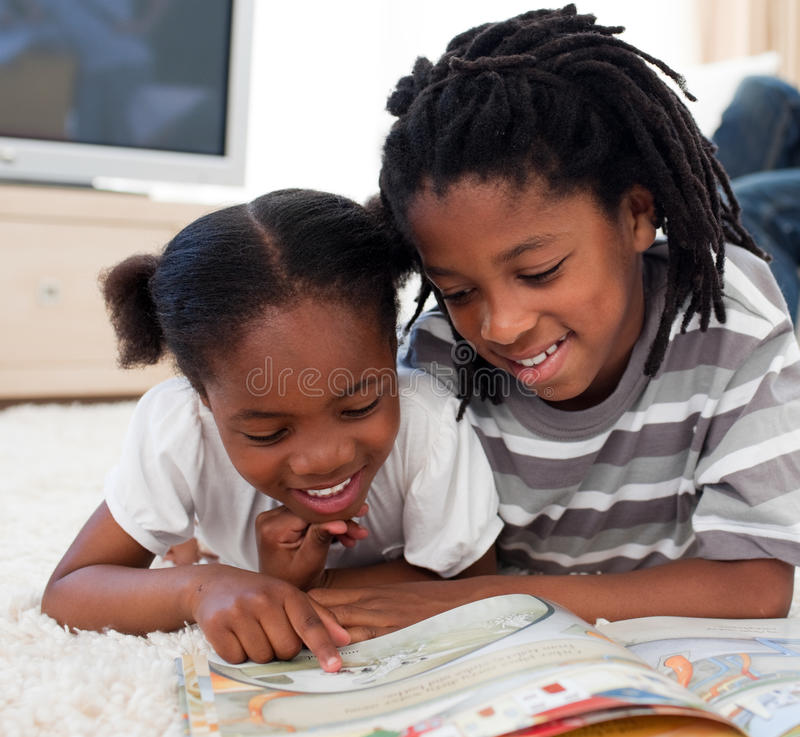 Free Happy Siblings Reading Lying On The Floor Stock Image - 12725841