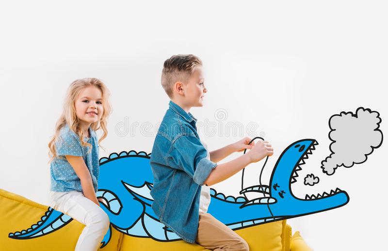 happy siblings riding drawn blue dragon while sitting royalty free stock photo