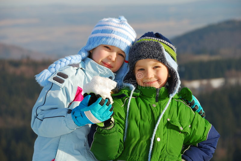 Happy siblings with snow stock photos