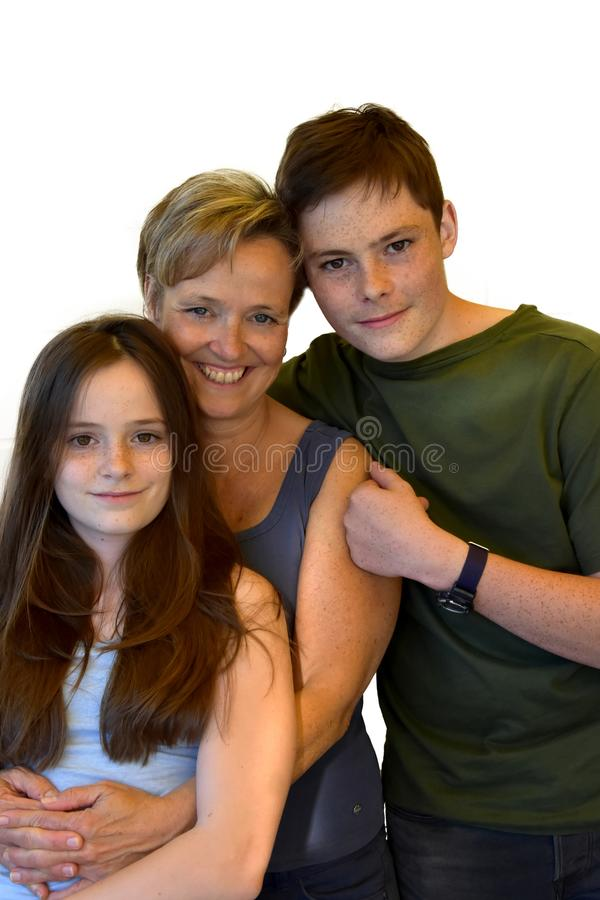 Happy siblings and their mother. Happy family, the big brother embraces his mother and his little sister on white stock photography