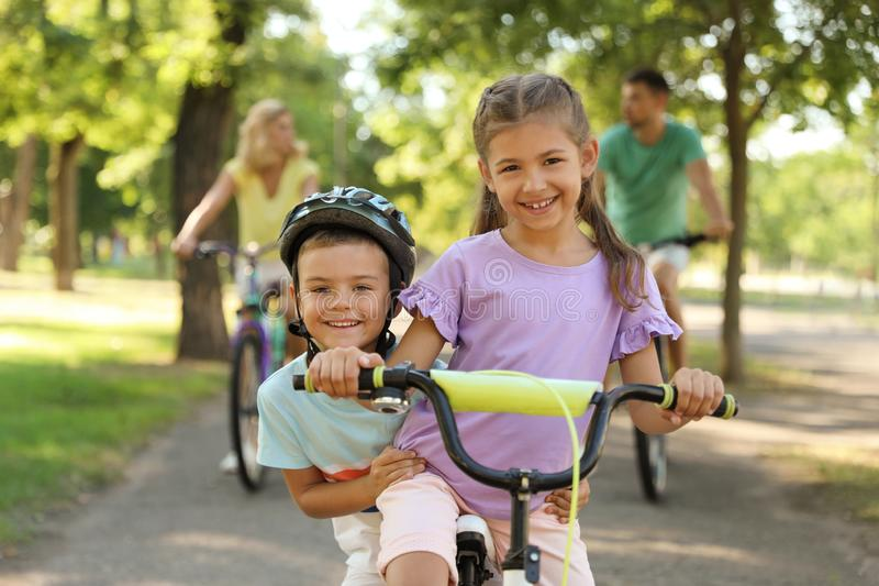 Happy siblings and their parents riding bicycles royalty free stock photography