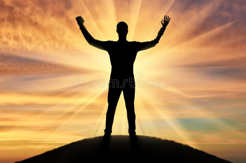 Happy silhouette of a disabled man with prosthetic hands on a hill royalty free stock image