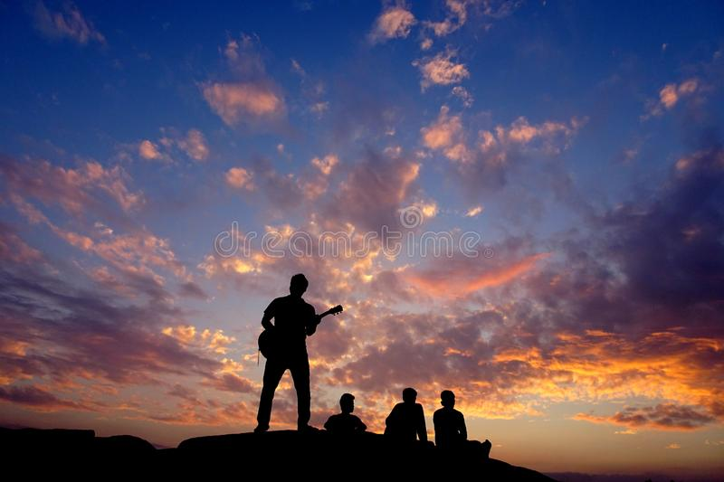 Happy silhouette friends people person having fun sitting on top of a rock hill mountain playing guitar guitarist musician , copy. Space on sunset orange fluffy stock photography