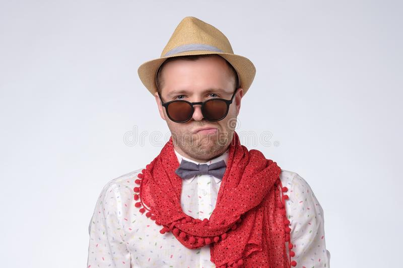 Happy and silly man dressed like a hippy pointing up at copyspace. Isolated on white stock photo
