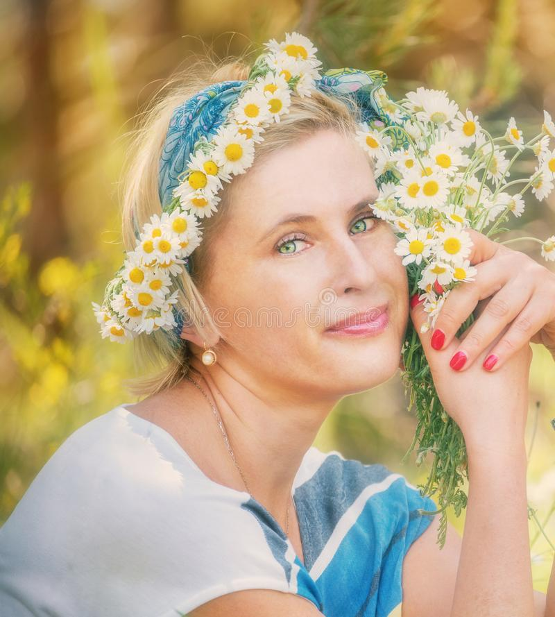 Happy simple woman on a summer meadow with a bouquet of daisies and a wreath of daisies. royalty free stock images