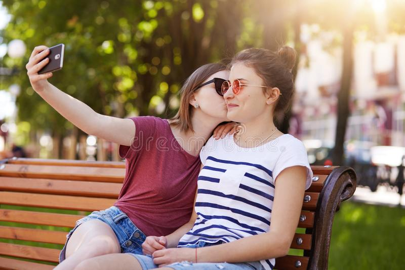 Happy sincere two girls make selfie on the wooden bench sitting in the park. Cheerful young girl kisses her best friend in right. Cheek while taking photo stock images