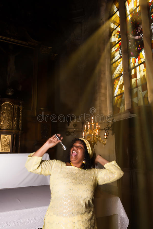 Happy Singer for the Lord. African-American gospel singer in a 17th century old church interior royalty free stock photos
