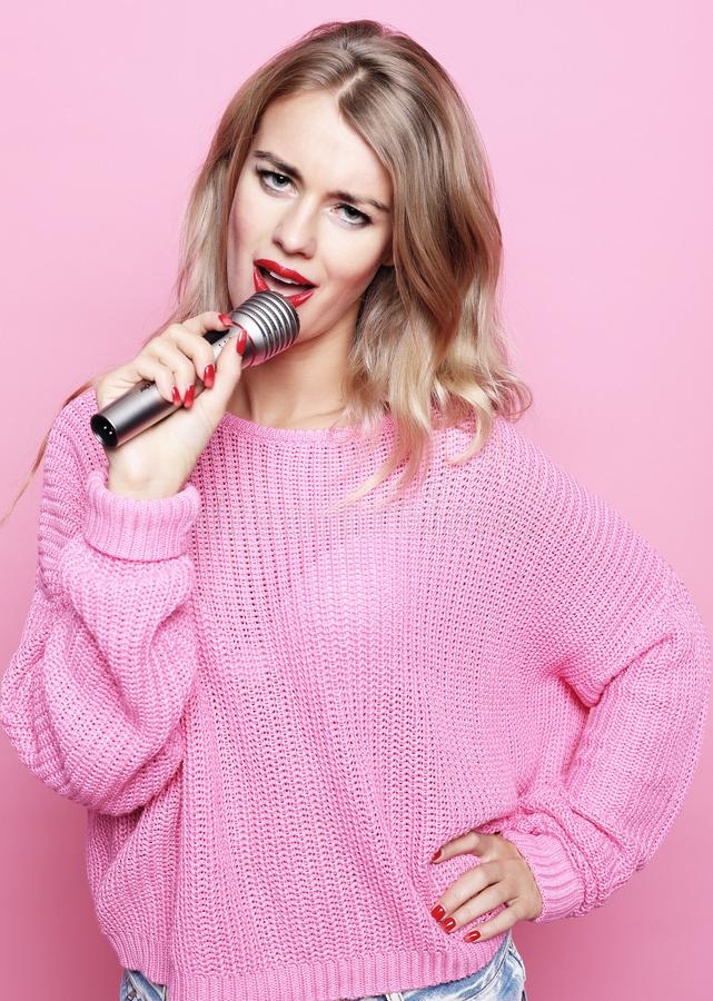 Happy singing girl. Beauty blond woman wearing pink pullover with microphone over pink background. close up. Happy singing girl. Beauty blond woman wearing pink stock images