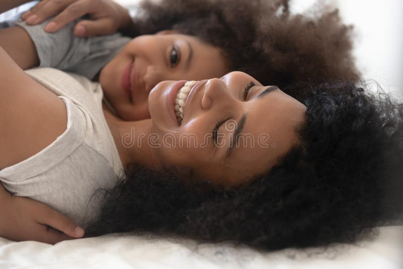 Happy single african american mommy lying on bed with daughter. stock photography