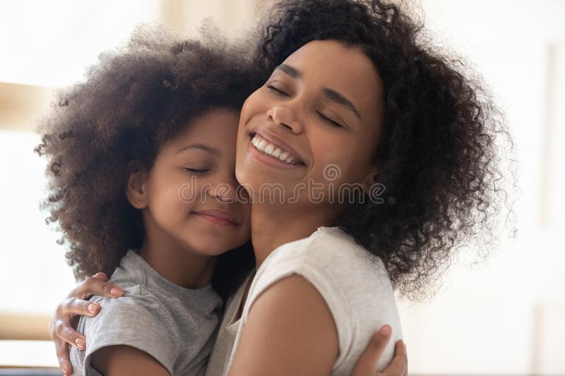 Happy single foster mother embracing cute little adopted daughter. stock photo