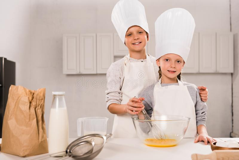 Happy sister and brother in aprons and chef hats whisking eggs in bowl at table. In kitchen stock photography