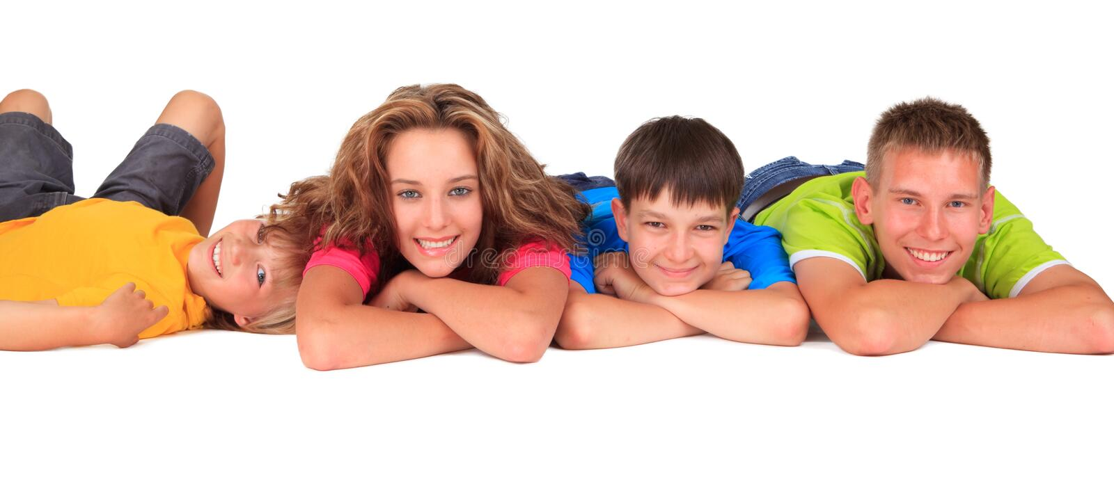 Happy sister and brothers. Lying in row on white studio background royalty free stock photo