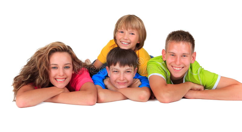 Happy sister and brothers. Happy sister lying with three young brothers, white studio background stock image