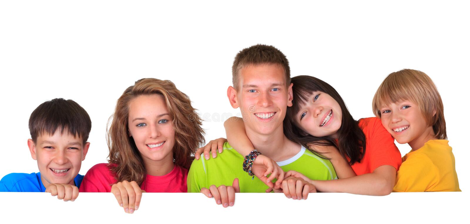 Happy sisters and brothers. Family of five happy brothers and sisters looking over blank white sign with copy space stock image