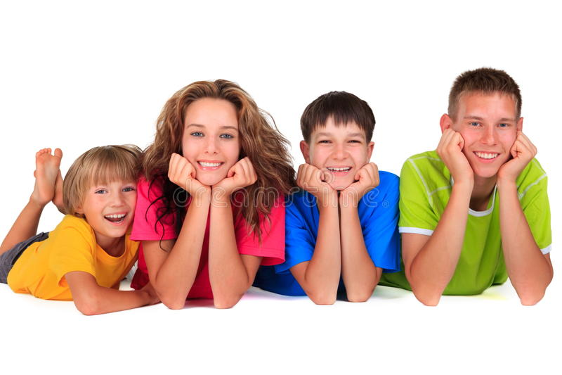 Happy sisters and brothers. Four happy young sisters and brothers of different ages in colorful clothes smiling in a line on white background stock photo