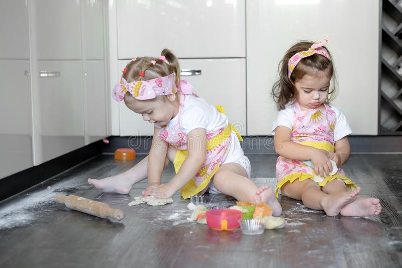 Happy sisters children girls bake cookies, knead dough, play with flour and laugh in the kitchen.  stock image