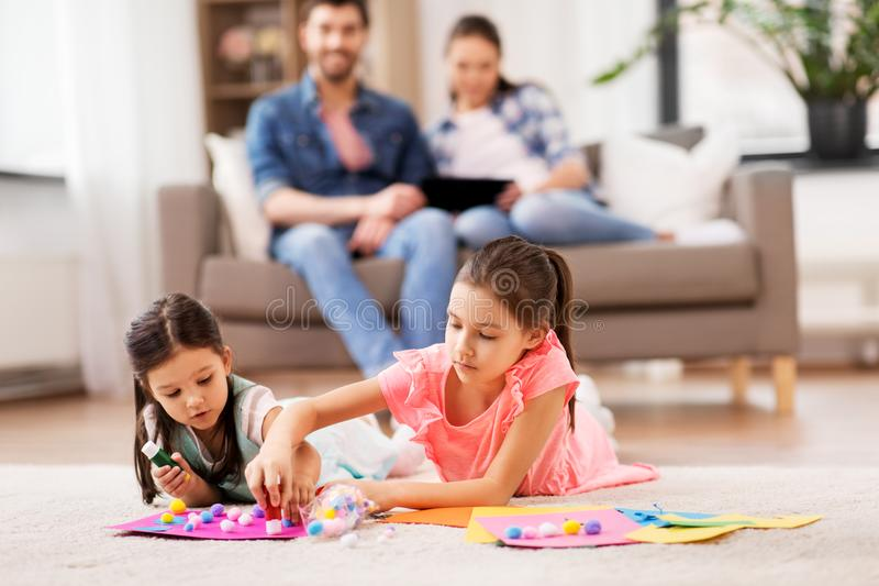 Happy sisters doing arts and crafts at home stock photography