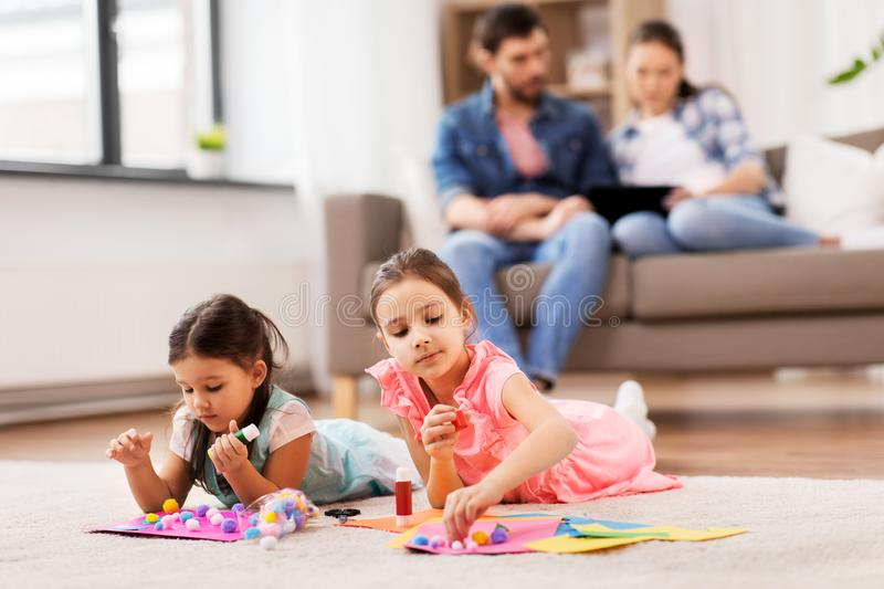Happy sisters doing arts and crafts at home stock image