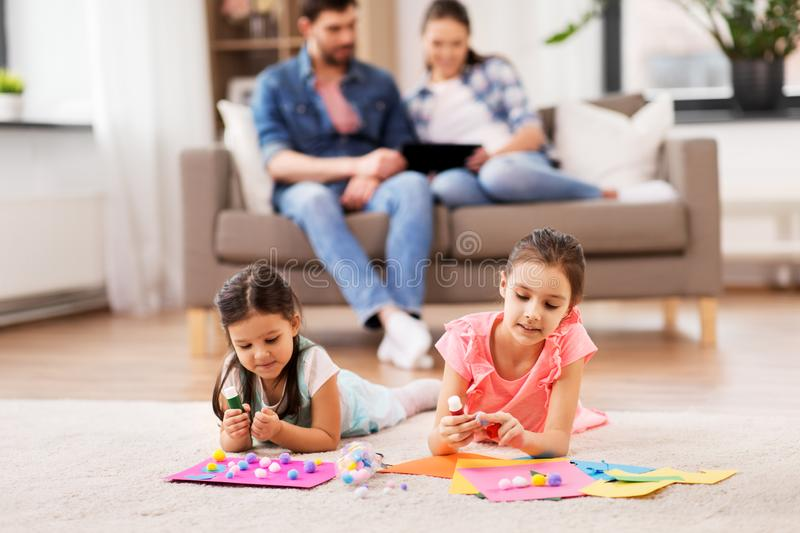 Happy sisters doing arts and crafts at home royalty free stock images