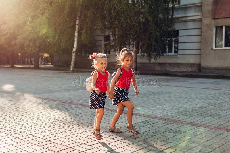 Happy sisters girls wearing backpacks and running. Children pupils having fun near school. Education royalty free stock images