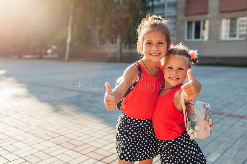 Happy sisters girls wearing backpacks and showing thumbs up. Kids pupils smiling outdoors school building. Education stock photography