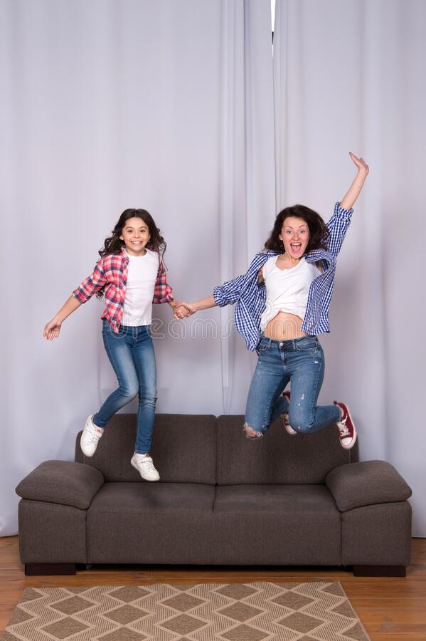 Happy sisters jump in freedom sense. mother and daughter having fun on weekend. move in new house. full of energy. real stock photo