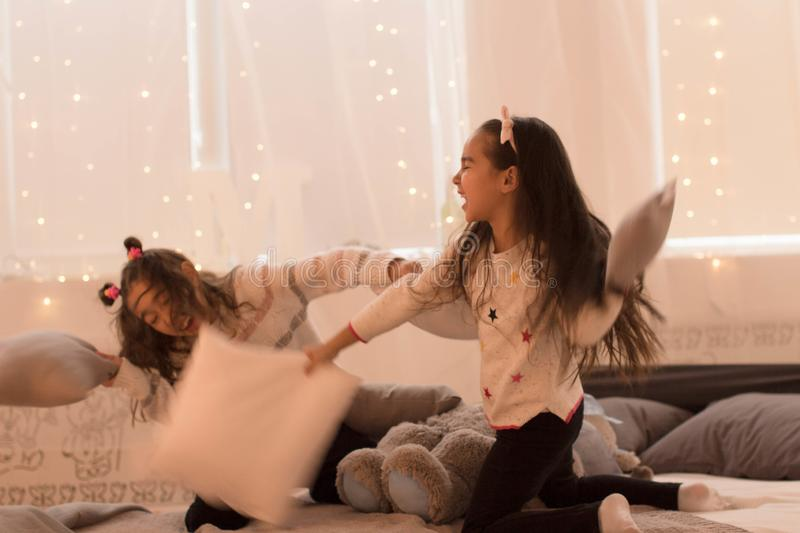 Happy sisters are playing in their room. Cute little girls fight pillows in a room in the evening dim light.  royalty free stock photos