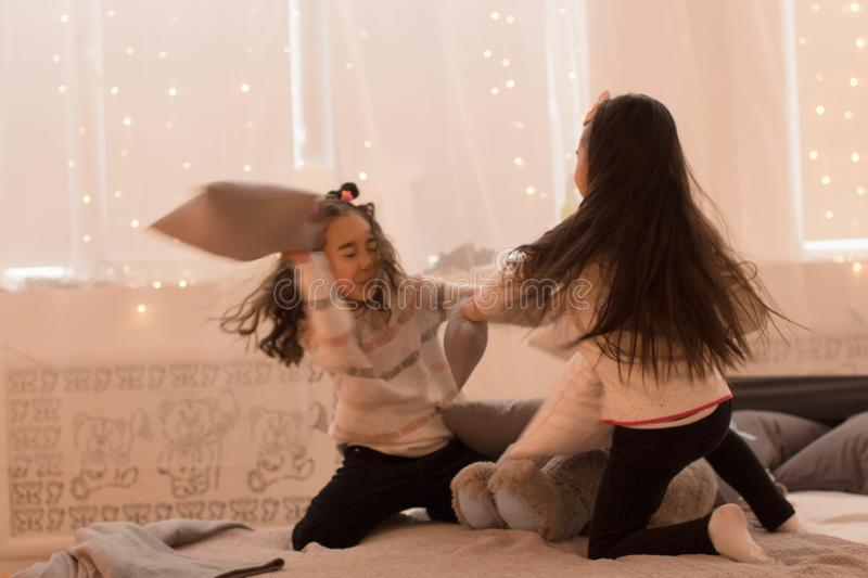 Happy sisters are playing in their room. Cute little girls fight pillows in a room in the evening dim light.  royalty free stock image