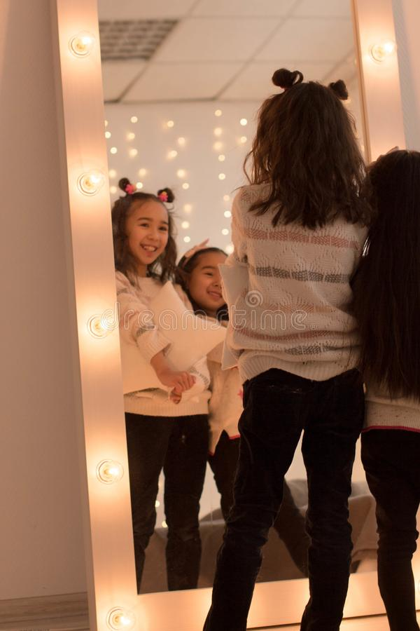 Happy sisters are playing in their room. Cute little girls near the mirror in the room in the evening dim light.  royalty free stock images
