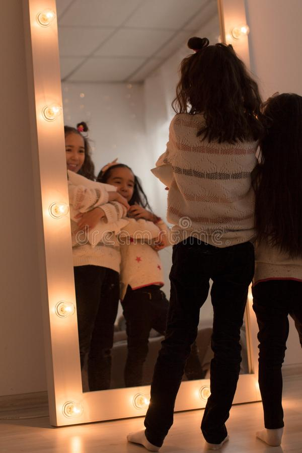 Happy sisters are playing in their room. Cute little girls near the mirror in the room in the evening dim light.  royalty free stock photo