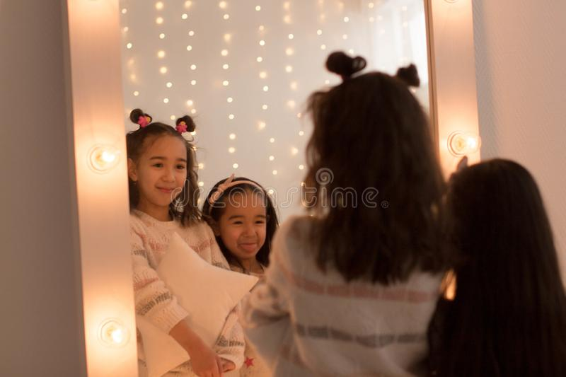 Happy sisters are playing in their room. Cute little girls near the mirror in the room in the evening dim light.  stock image