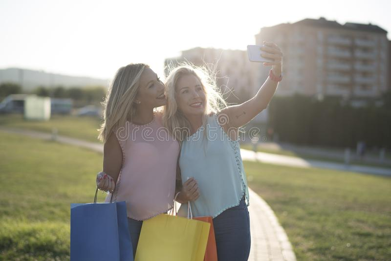Happy sisters taking selfie after shopping royalty free stock images