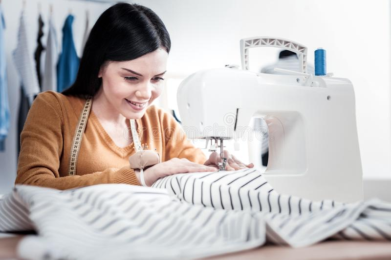 Happy skilled tailor using professional equipment stock photography